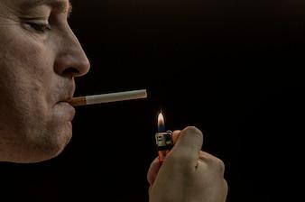 Homem que fuma cigarro no fundo preto. Homem misterioso com charuto e fumo isolado no fundo preto. Tiro escuro e mal-humorado de um jovem fumando sobre um fundo preto