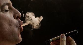 Homem que fuma cigarro no fundo preto, Homem novo bonito que fuma cigarro, Homem misterioso com charuto e fumo isolado no fundo preto