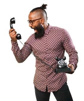 Homem que grita em um telefone antigo