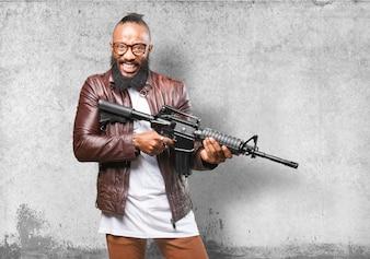 Homem que ri enquanto segura uma arma automática