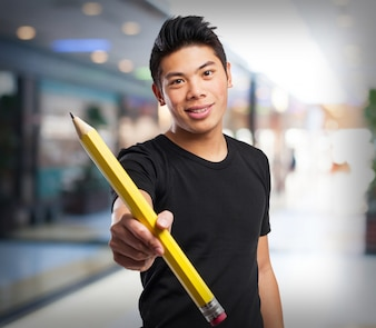 Homem segurando um lápis gigante