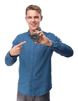 Homem segurando uma bússola com uma mão e sorrindo