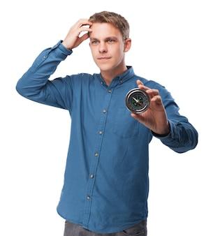 Homem segurando uma bússola com uma mão