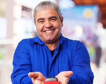 Homem sênior de sorriso com um carrinho de brinquedo vermelho