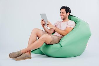 Homem sorridente no sofá com tablet