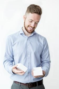 Homem sorridente segurando pequena caixa vazia