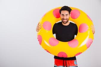 Homem sorrindo em roupas de praia com tubo flutuante