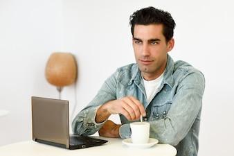 Homem tomando café com um laptop ao lado dele