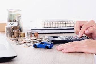 Homem usando calculadora com brinquedo de carro e pilha de moedas para empréstimo de seguro ou Economia para comprar conceito de carro
