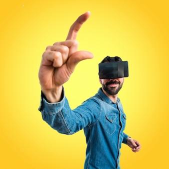 Homem usando óculos VR segurando algo em fundo colorido