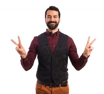 Homem vestindo colete fazendo um gesto de vitória