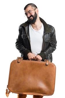 Homem vestindo uma jaqueta de couro segurando uma mala