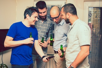 Homens assistindo o smartphone na festa