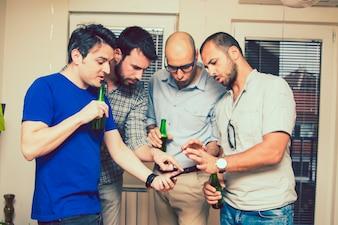 Homens com cerveja e smartphone na festa