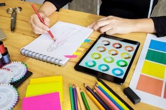 Homens trabalhando como designer de moda escolhendo no gráfico de cores para roupas em tablet digital no estúdio do local de trabalho.