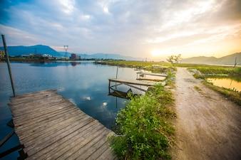 Imagem bonita do céu do sol atrasado sobre a paisagem do lago calmo com ca