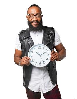 Indivíduo de sorriso com colete mostrando um relógio