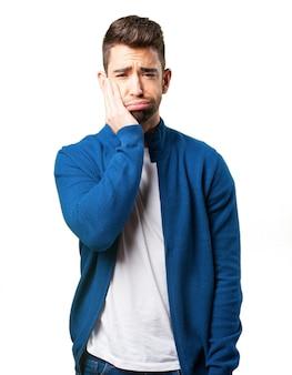Indivíduo em um casaco azul com dor de dente