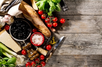 Ingredientes alimentares italianos deliciosos e deliciosos para cozinhar no antigo fundo de madeira rústica.