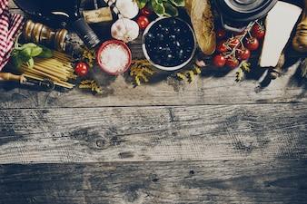Ingredientes alimentares italianos saborosos saborosos e saborosos sobre o antigo fundo de madeira rústica. Pronto para cozinhar. Conceito de culinária italiana italiana. Toning.