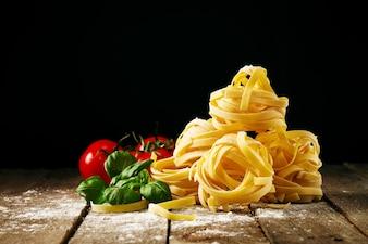 Ingredientes coloridos frescos saborosos para cozinhar Tagliatelle da massa com manjericão fresco e tomates. Horizontal. Fundo De Madeira Da Tabela.