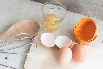 Ingredientes e ferramentas para fazer um bolo, ovos, copos de padaria