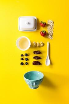 Ingredientes naturais saborosos e saudáveis para o café da manhã em fundo vibrante amarelo. Pequeno-almoço Morning Food Concept.
