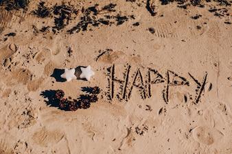 """Inscrição """"FELIZ ANO NOVO"""" e pegada humana na areia da praia"""