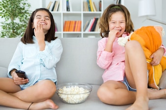 Irmãs novas bonitas que comem pipoca em casa.