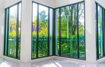 Janela de vidro com vista para jardim verde.