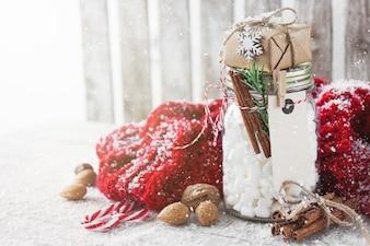 Jarra de vidro cheia de algodão com um presente em cima