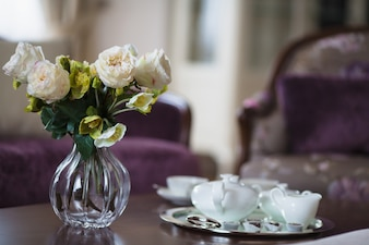 Jarro de vidro com flores e copos de café
