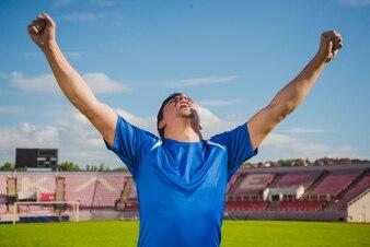 Jogador de futebol comemorando a vitória