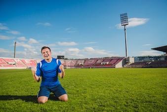 Jogador de futebol comemorando joelhos
