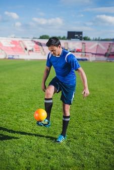 Jogador de futebol de malabarismo em um estádio