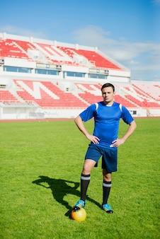 Jogador de futebol posando no estádio