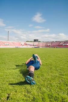 Jogador de futebol que estica as pernas