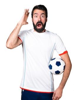 Jogador de futebol segurando uma bola de futebol fazendo um gesto de surpresa