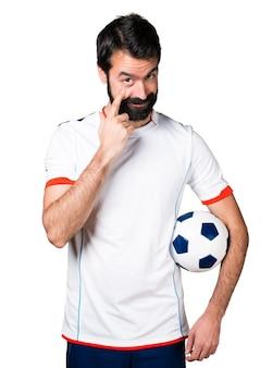 Jogador de futebol segurando uma bola de futebol mostrando algo