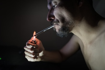 Jovem adulto fumando no quarto escuro.