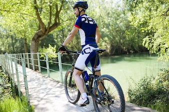 Jovem apaixonado relaxando após o ciclismo na montanha.