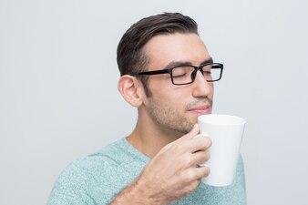 Jovem atraente que aprecia o cheiro de chá