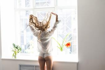 Jovem, bonita, de pé na janela aberta e olhando para fora, gosta de descansar