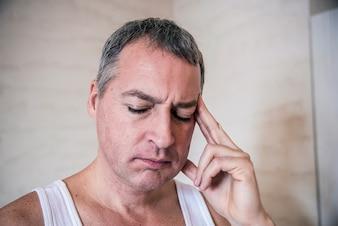 Jovem bonito tocando sua cabeça com uma mão com forte dor de cabeça, foto de perto. Sentindo-se cansado. Esforço, dor de cabeça, desespero, tristeza e conceito de pessoas