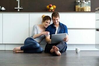 Jovem casal bonito usando comprimidos digitais na cozinha em casa.