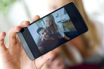Jovem casal bonito usando o telefone móvel em casa.
