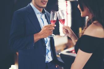 Jovem casal de negócios com copos de champanhe.