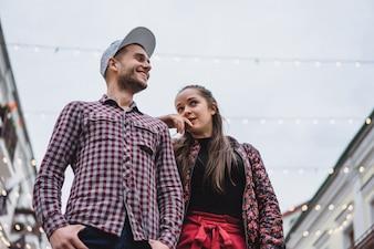 Jovem casal elegante posando ao ar livre. Um jovem com uma cerda em uma touca com uma menina com cabelos longos. Jovens felizes estão caminhando pela cidade. retrato. fechar-se.