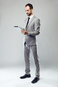 Jovem de negócios usando seu tablet digital sobre fundo cinza.