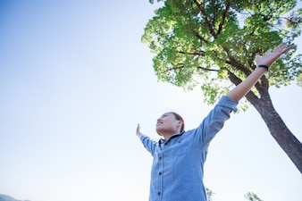 Jovem de pé olhando para um céu com as mãos levantadas enquanto faz caminhadas na montanha.